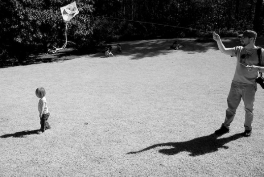 Mark flying a kite. Lili walking about aimlessly.